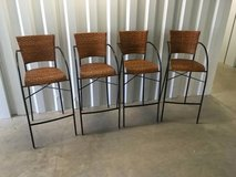 Four Wicker and black metal barstools in Joliet, Illinois