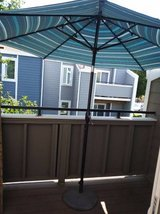 Out door umbrella with heavy duty cast iron stand in Vacaville, California