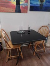 Square black table with two basic maple chairs in Beale AFB, California